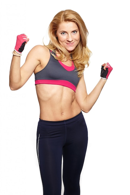Photo of attractive young fitness woman lifting dumbbell in bright cloth Free Photo