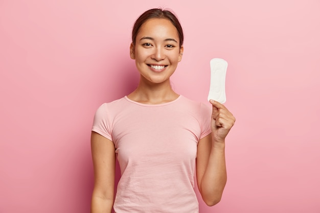 Photo of attractive young lady with asian appearance, holds clean sanitary napkin, satisfied with its quality, uses intimate product during menstruation or periods, isolated on pink wall Free Photo
