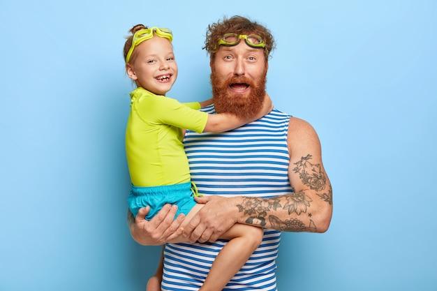 La foto del giovane padre barbuto indossa occhiali e gilet a righe, trasporta la piccola figlia, trascorre attivamente le vacanze estive, nuota, si ama, isolato sul muro blu. concetto di famiglia Foto Gratuite