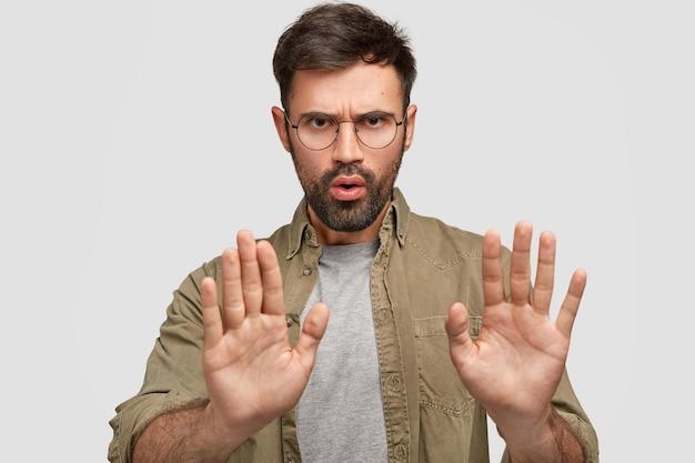 La foto di un giovane maschio barbuto mostra il gesto di arresto, ha un'espressione del viso dispiaciuta, nega qualcosa, parla di cose proibite, indossa una camicia alla moda, isolato su un muro bianco Foto Gratuite