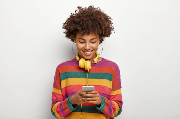Photo of beautiful afro american woman concentated into smartphone device, enjoys chatting online, downloads music to playlist for listening in headphones, has curly dark hair, wears casual outfit Free Photo