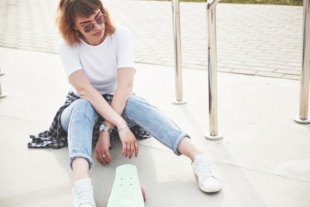 Una foto di una bella ragazza con bei capelli tiene uno skateboard su una lunga tavola e sorridente, vita urbana. Foto Gratuite