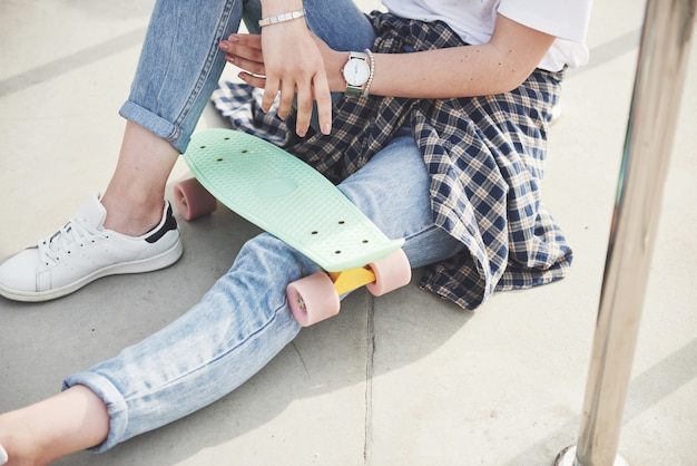 Una foto di una bella ragazza con bei capelli tiene uno skateboard su una tavola lunga Foto Gratuite