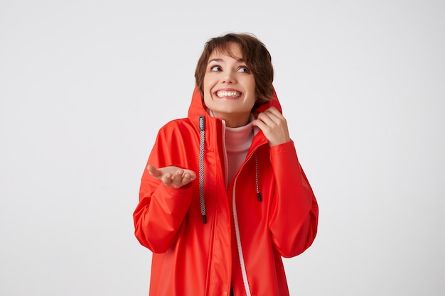 Photo of beauty young smiling short haired woman in red rain coat, looking up to the left, hides in the hood, puts the palm under the rain.standing. Free Photo