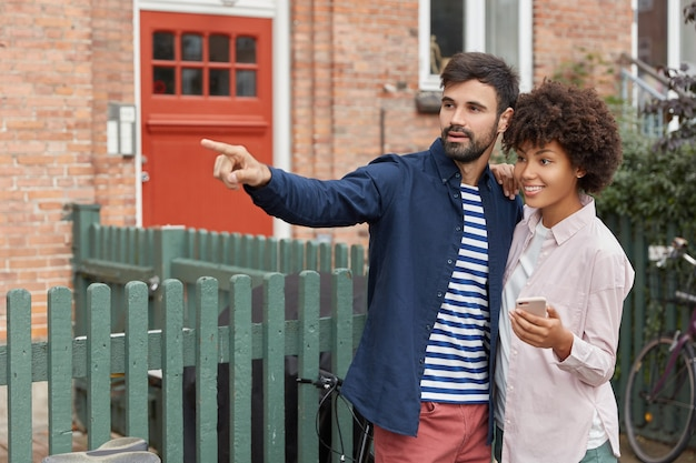 Photo of black woman and caucasian guy have outdoor walk, stand closely Free Photo