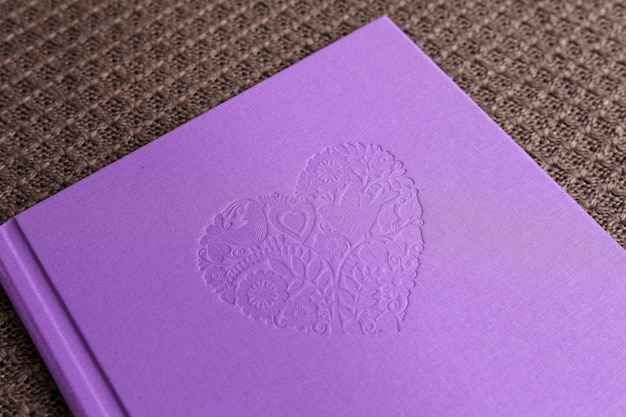 Photo book with textile cover.  violet color with decorative stamping. Premium Photo