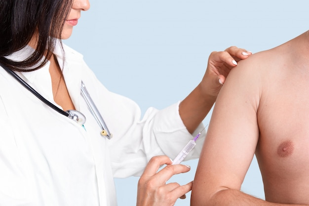 Photo of brunette female nurse in white gown with phonendoscope, makes vaccination in arm to patient Free Photo