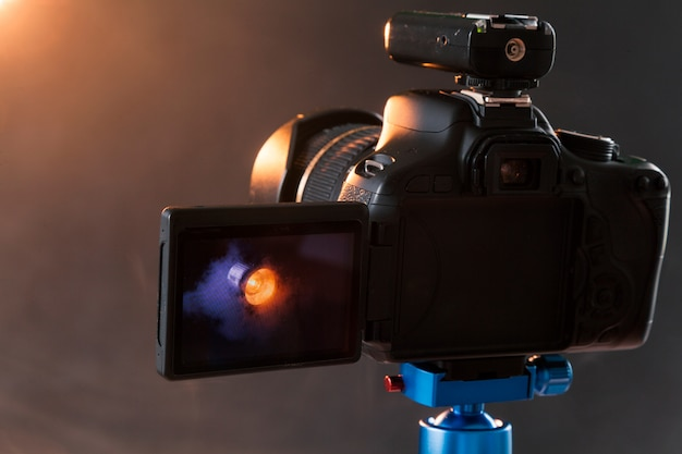 Photo of the camera on a blue tripod that photographs in the studio a professional lighting device in the smoke. studio lights and smoke equipment. advertising photo session of the lighting device Premium Photo