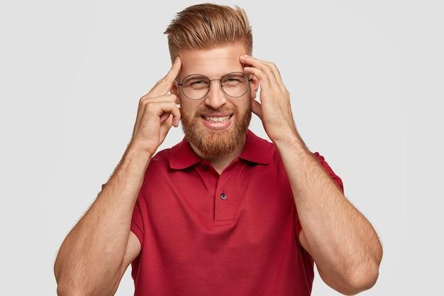La foto di un allegro giovane hipster dai capelli rossi ha una cattiva memoria, tiene le mani sulle tempie, cerca di ricordare qualcosa, ha un sorriso amichevole, indossa abiti casual, sta da solo contro il muro bianco. Foto Gratuite
