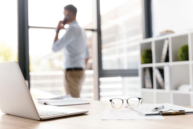 사무실 물건을 테이블에 누워 직장의 사진 근접 촬영, Defocused 비즈니스 남자가 스마트 폰에 말하기와 큰 창문을 통해보고 프리미엄 사진