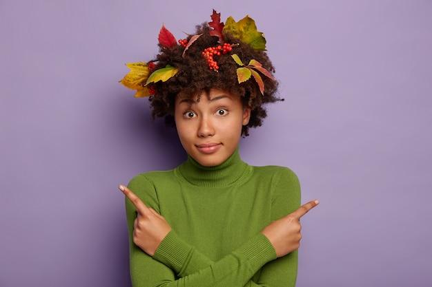 Foto di donna dalla pelle scura confusa con foglie di autunno nei capelli, attraversa le mani sul petto, punta lateralmente, indossa un maglione verde, isolato su sfondo viola. Foto Gratuite