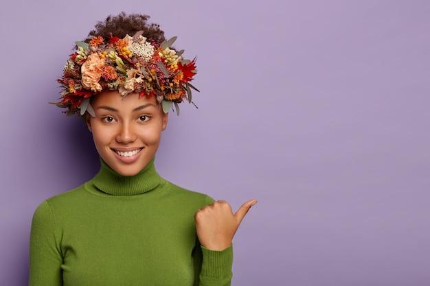 La foto di una giovane donna riccia dalla pelle scura punta il pollice lontano, indossa dolcevita verde, ghirlanda autunnale, ha un sorriso piacevole, mostra spazio per copiare i tuoi contenuti pubblicitari, dà suggerimenti Foto Gratuite