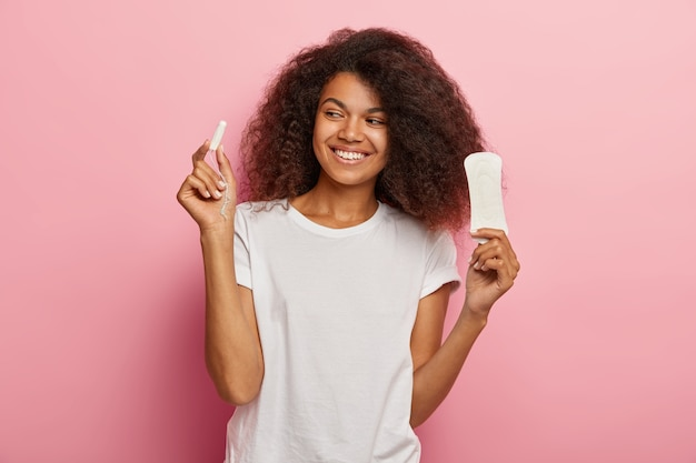 Photo of delighted african american woman holds tampon and sanitary napkin, dressed in white t shirt, isolated over pink wall. women, pms Free Photo