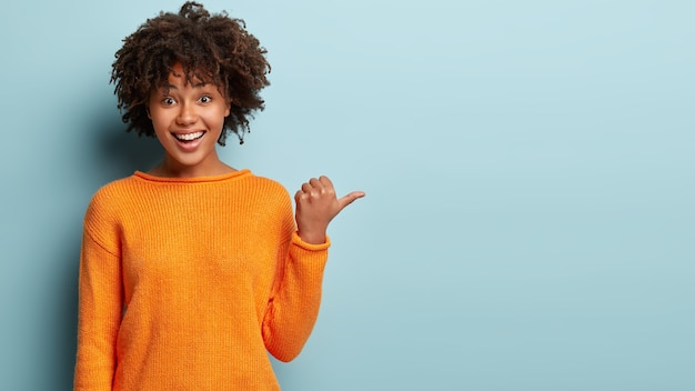 Photo of delighted cheerful afro american woman with crisp hair, points away, shows blank space, happy to advertise item on sale, wears orange jumper, demonstrates where clothes shop situated Free Photo