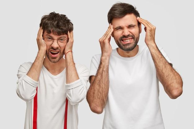 Le foto di maschi delusi hanno un terribile mal di testa, tengono le mani sulle tempie, si accigliano, si sentono insoddisfatti e oberati di lavoro, indossano abiti casual, isolati su un muro bianco. emozioni negative Foto Gratuite