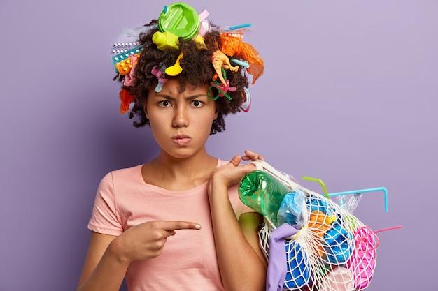 Foto di una donna afroamericana dispiaciuta arrabbiata per l'uso abusivo della plastica, indica la borsa con la spazzatura raccolta, ha rifiuti in testa, isolata sul muro viola. concetto di inquinamento non riciclabile Foto Gratuite