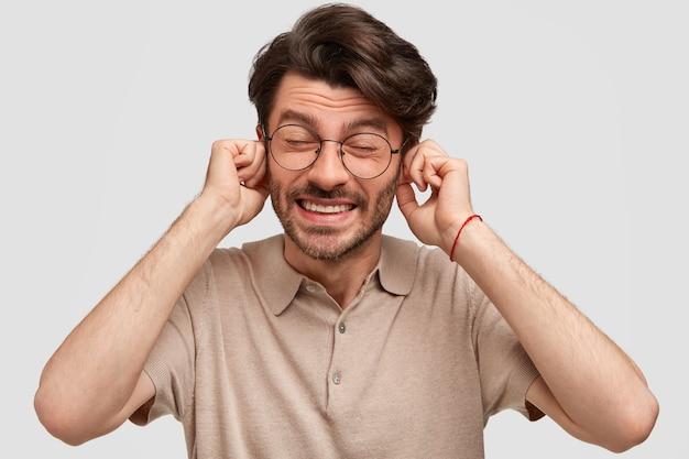 La foto di un uomo scontento tappi le orecchie con insoddisfazione, ignora qualcuno Foto Gratuite