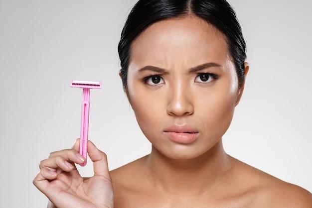 Photo of displeased woman showing razor Free Photo