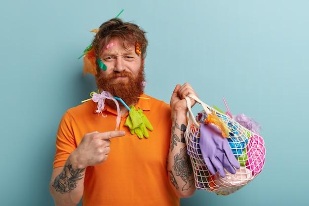 Foto di un uomo insoddisfatto dai capelli rossi con setole spesse, punta il dito anteriore verso un sacchetto pieno di rifiuti di plastica, indossa una maglietta arancione casual, ha un braccio tatuato, si trova sopra il muro blu. giorno della terra Foto Gratuite