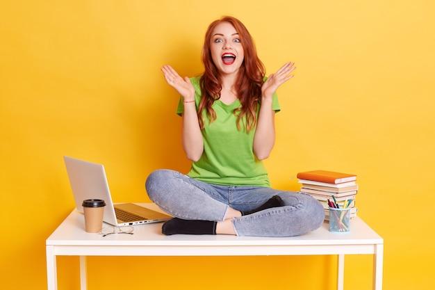 Foto della ragazza eccitata dell'allievo che si siede allo scrittorio circondato con i quaderni, la parte superiore del computer portatile, il caffè, mantenendo la bocca ampiamente aperta e diffondendo le palme da parte, isolate su sfondo giallo. Foto Gratuite