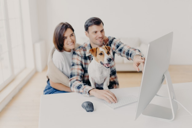 Photo of family couple make shopping on favourite website, enjoy time together, funny dog focused in monitor of computer, sits in coworking space. Premium Photo