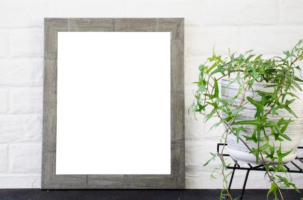 コンクリートフレームのフォトフレームと美しい植物 Premium写真