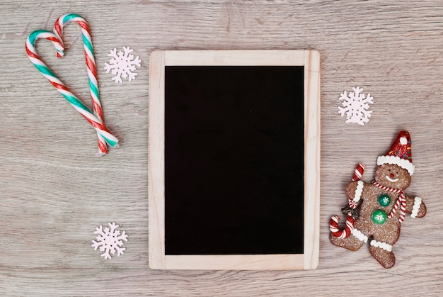 Photo frame between candy canes placed in form of heart and cookie snowman Free Photo