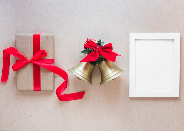 Photo frame between christmas bells and gift box Free Photo