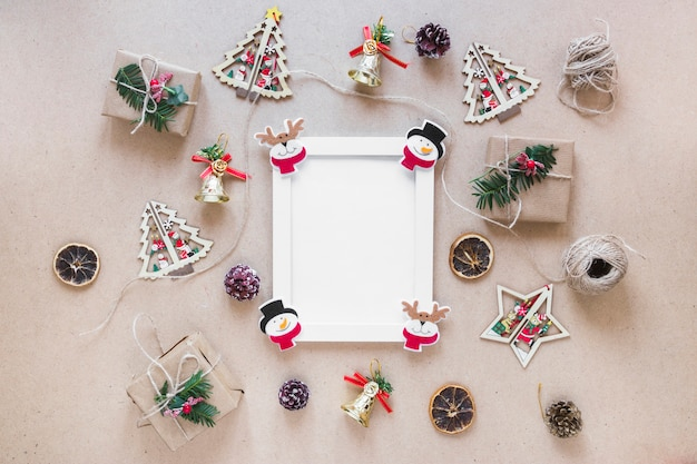 Photo frame between christmas decorations and gift boxes Free Photo