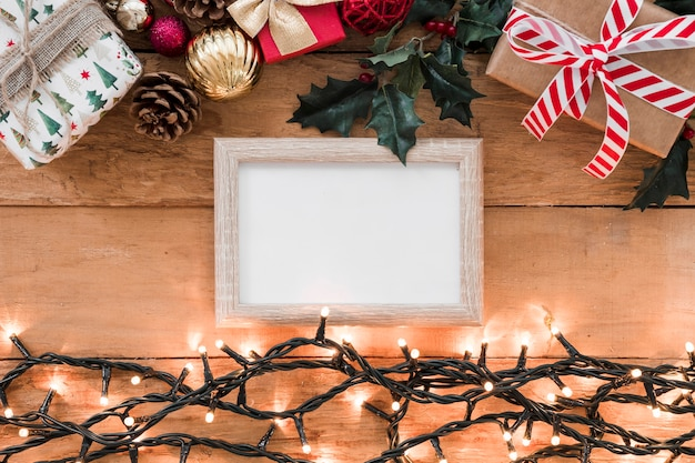 Photo frame between christmas decorations and illuminated fairy lights Free Photo