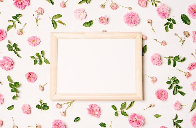 Photo frame between collection of pink flowers and green leaves Free Photo