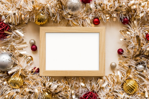 Photo frame between decorative gold tinsel with ornament balls Free Photo