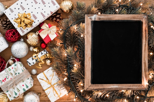 Photo frame on fir twigs between fairy lights near christmas decorations Free Photo