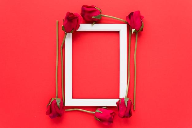 Photo frame between fresh flowers Free Photo