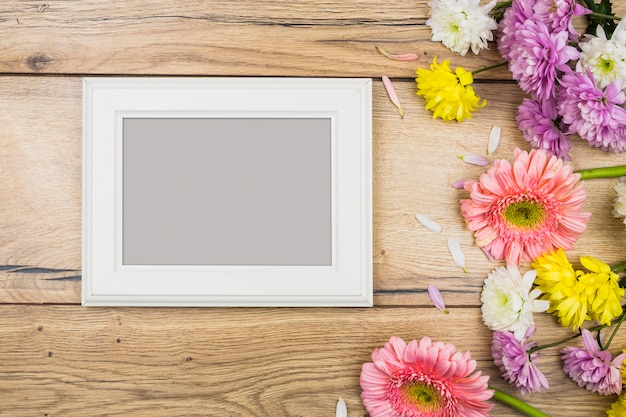 Photo frame near fresh bright flowers on desk Free Photo