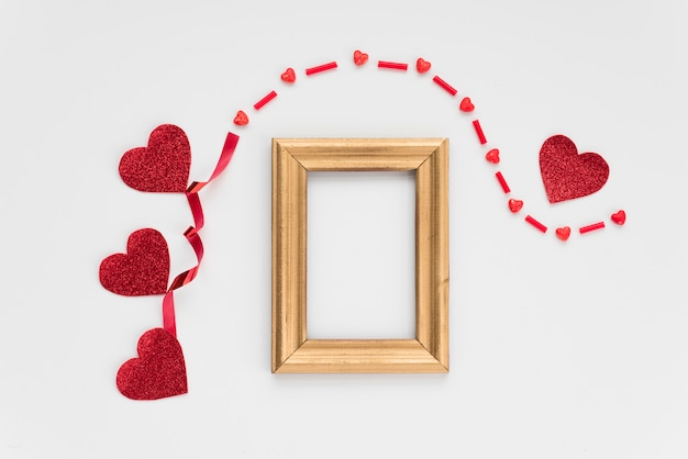 Photo frame near ornament hearts and band Free Photo