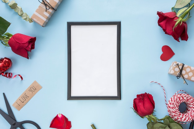 Photo frame near scissors, roses and bobbin of twists Free Photo