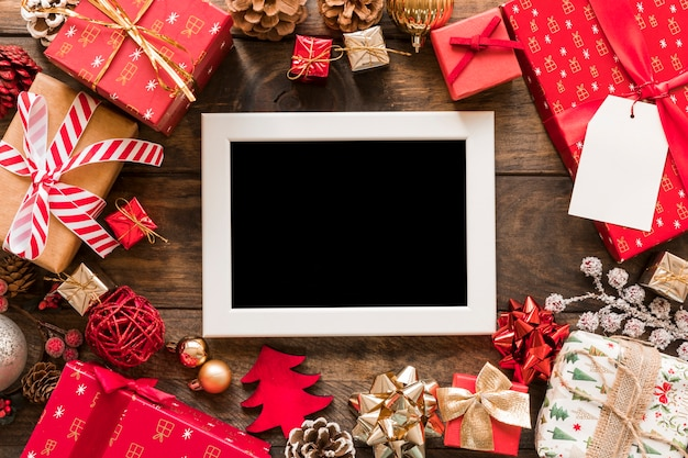Photo frame near set of gift boxes and christmas decorations Free Photo