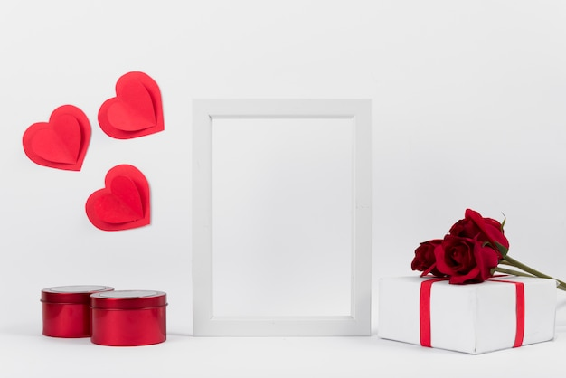 Photo frame between present with flowers, paper hearts and boxes Free Photo