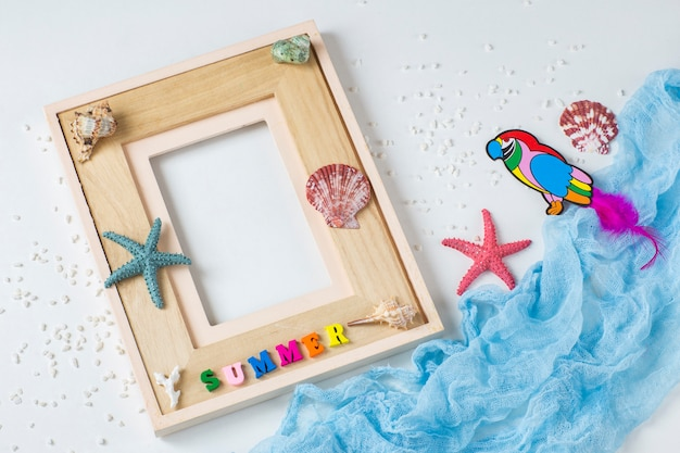 Photo frame, starfish, shells, the word summer, sand and a parrot. about summer vacation, memories Premium Photo