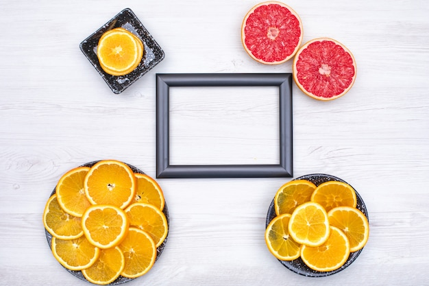 Photo frame surrounded with orange slices in black plate and two slice of grapefruit on wooden  surface Free Photo