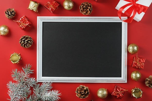 Photo frame with free black space around christmas decorations and gifts on a red background. top view, free space for text Premium Photo