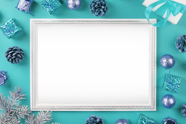 Photo frame with free white space around christmas tree decorations and gifts on a blue background. top view, free space for text Premium Photo