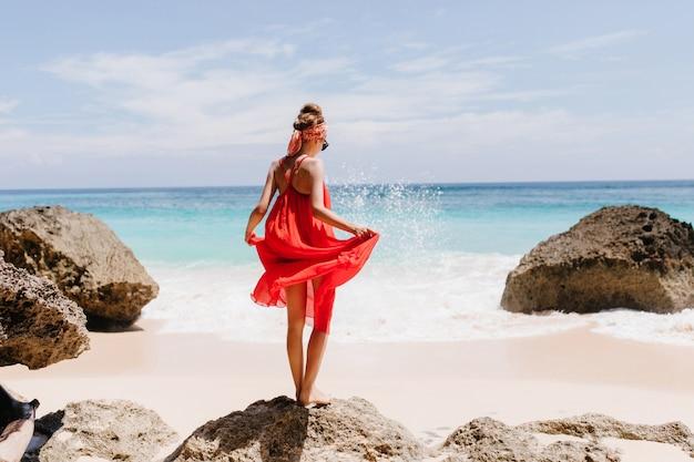 Фотография со спины стройной загорелой девушки, стоящей на большом камне. открытый выстрел изящной женской модели, играющей с ее красным платьем и смотрящей на океанские волны. Бесплатные Фотографии