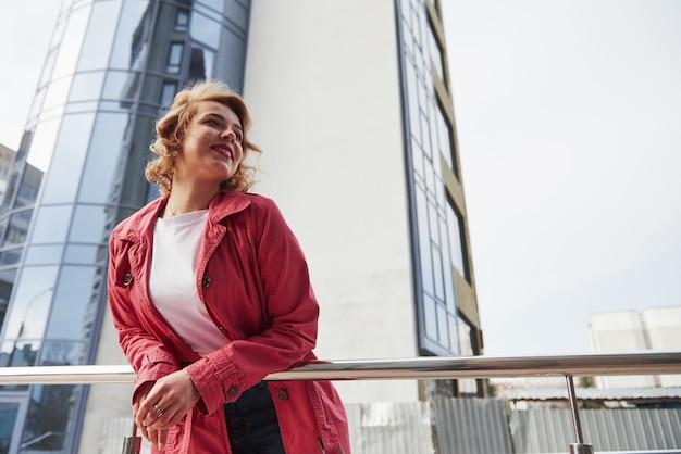 下からの写真。暖かい赤いコートを着た大人のきれいな女性が彼女の週末の時間に街を歩いている 無料写真