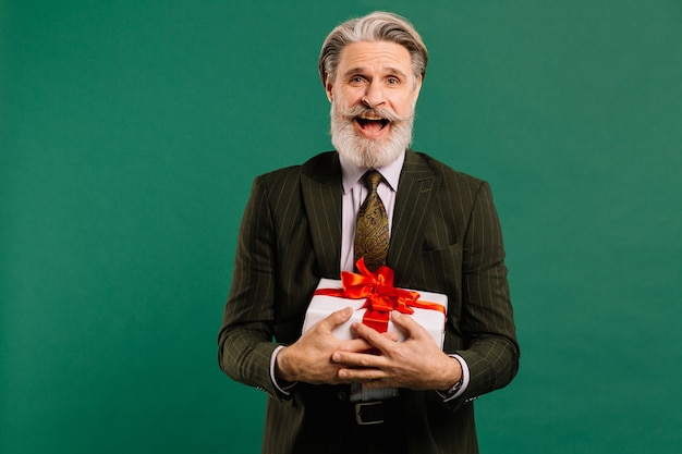 Photo of funky mature guy amour in khaki suit cupid character role showing big gift box on a valentine day isolated green color background Premium Photo