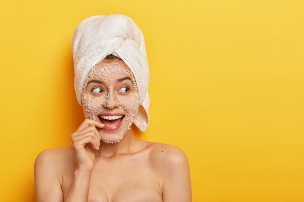 Photo of glad european girl with toothy smile, uses sea salt for spa procedures, takes shower, has smooth healthy skin, looks away, wears white towel, isolated over yellow background. beauty concept Free Photo