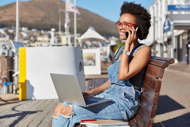 Foto di un adolescente afroamericano felice e sorridente chiama qualcuno tramite il cellulare, tiene il computer portatile sulle ginocchia, si siede a una panchina all'aperto usa gadget per studiare online, bloggs. moda, lifestyle, tecnologia Foto Gratuite