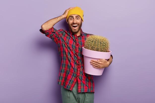 La foto di un giovane felice con la barba lunga tiene la mano sulla testa, porta un vaso di piante verdi, riceve un cactus con spine spinose come regalo, indossa un cappello giallo e una camicia rossa intrecciata, si preoccupa della pianta in vaso Foto Gratuite