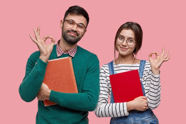La foto dello studente maschio bello e della sua compagna di gruppo dimostra il gesto giusto, d'accordo con qualcosa Foto Gratuite
